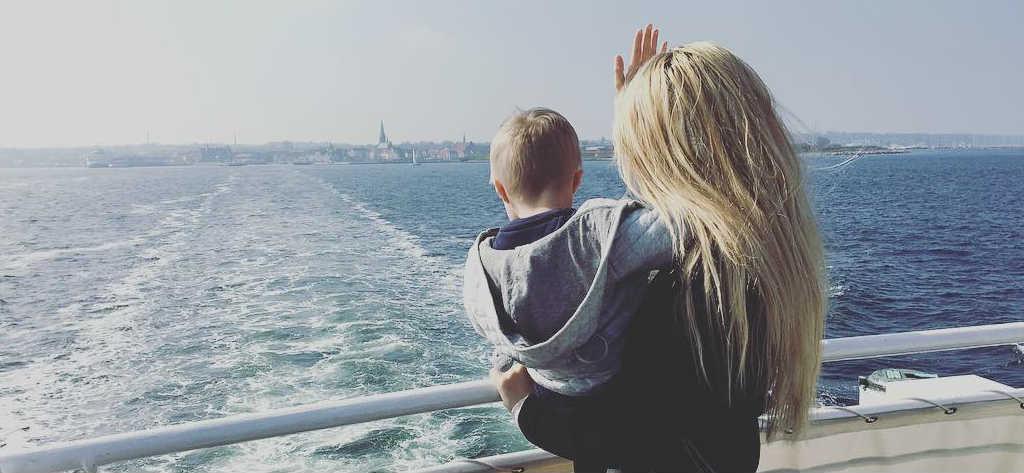 Julia Bergman och hennes son Milan vinkar från en båt