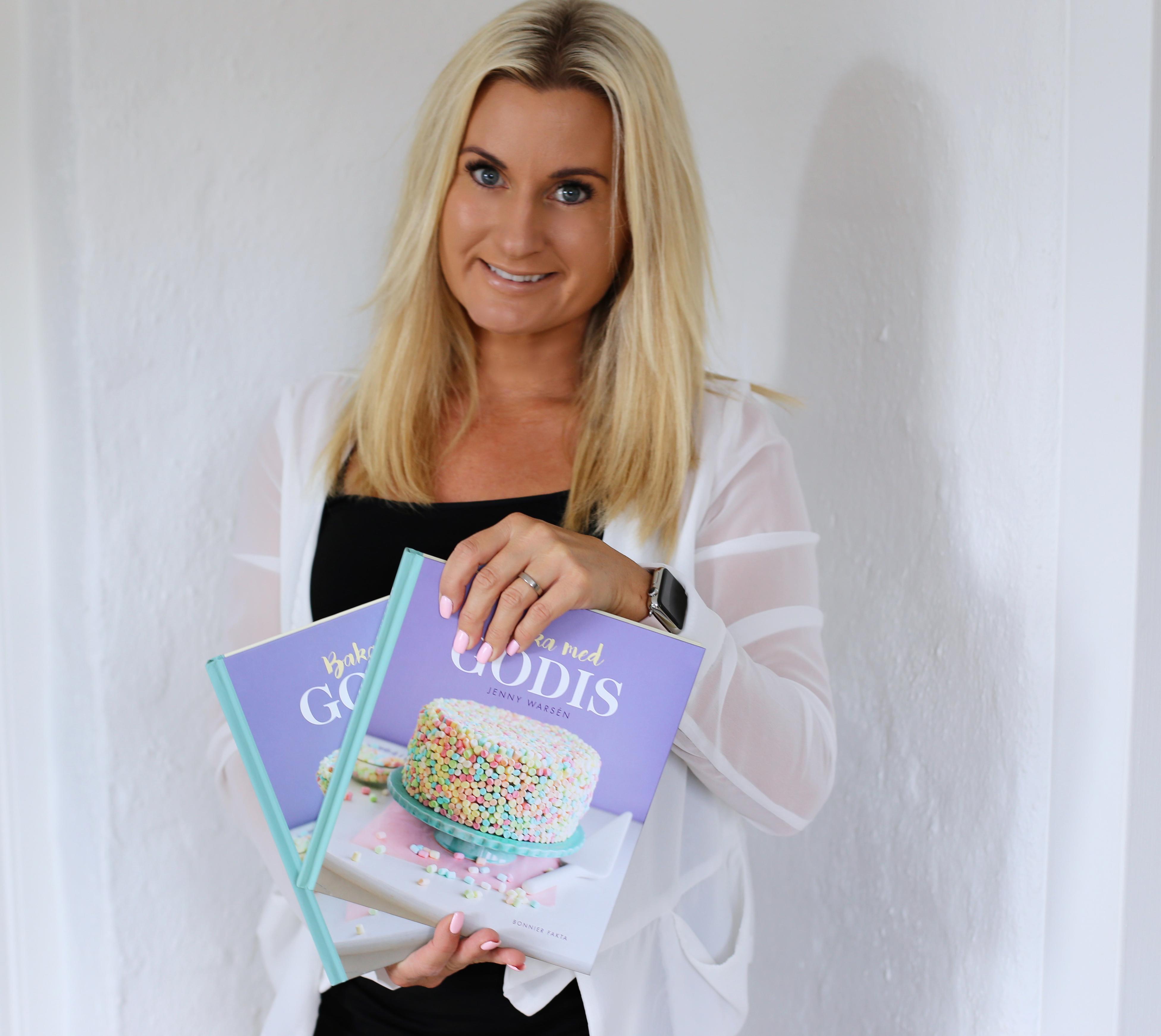 Jenny Warsen, som driver Jennys Matblogg, håller två exemplar av sin bok Baka med godis