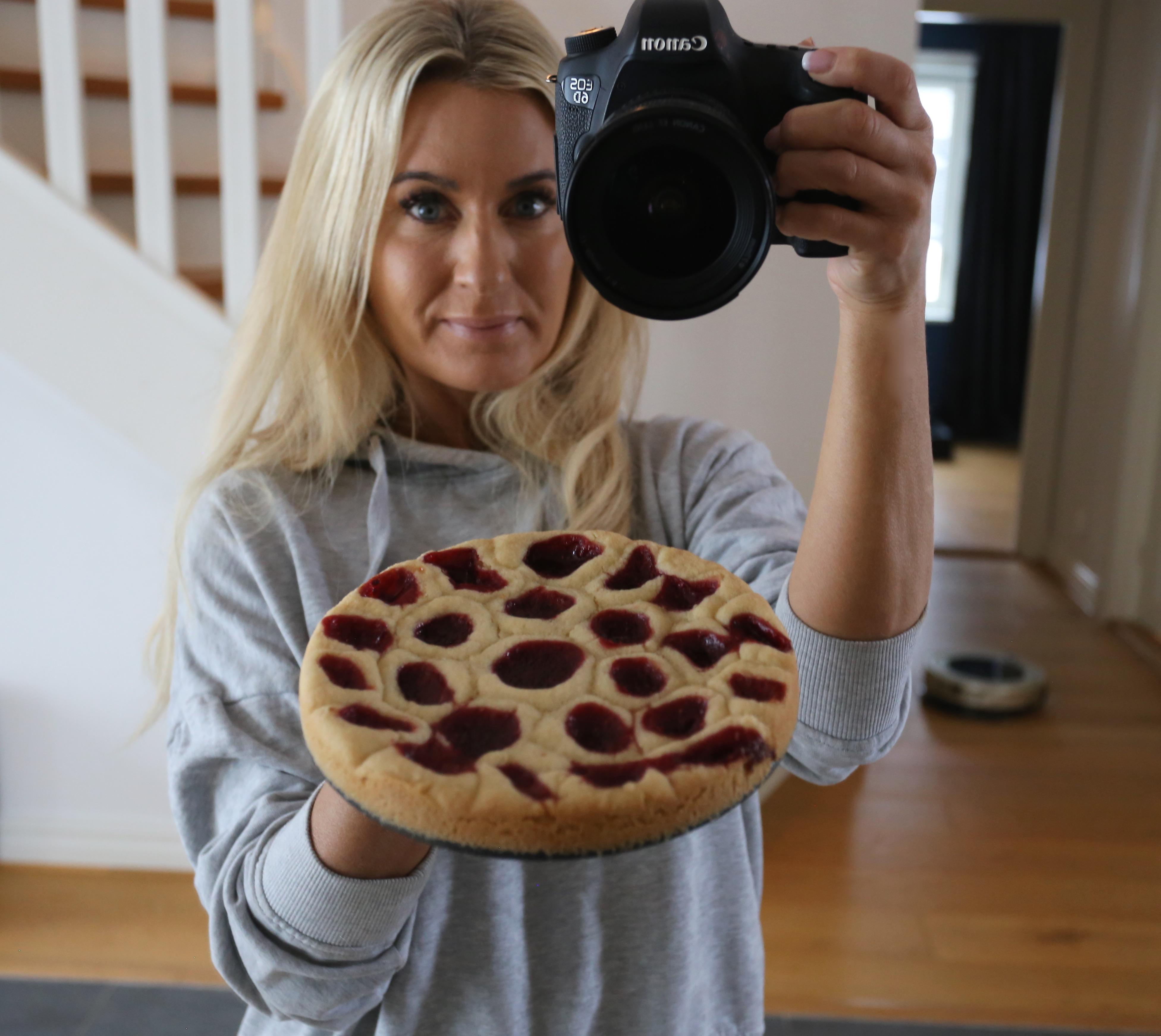 Jenny Warsen, som driver Jennys Matblogg, håller upp en paj och fotar sig själv i spegeln