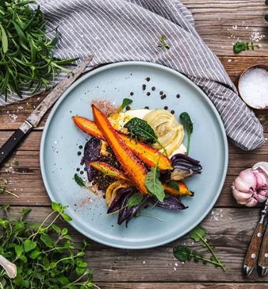 Grillande morötter, fänkål och andra grönsaker från Landleys Kök på en ljusblå tallrik