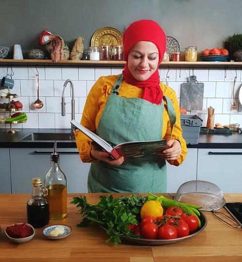 Zeina Mourtada, som driver Zeians Kitchen, läser ur en av sina kokböcker bakom ett bord med ett grönsaksfat