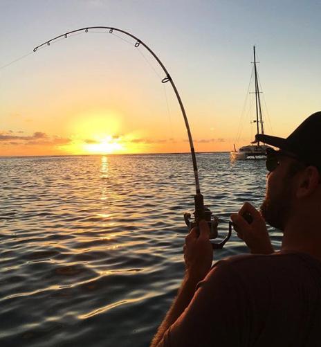 Man i keps och solglasögon från Instagramkontot Arga Skånska Män fiskar medan solen går ner i horisonten.