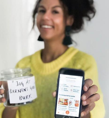 Vivi Wallin, som driver MammaSanningar, håller fram en mobiltelefon samt en glasburk med texten Jag åt barnens godis