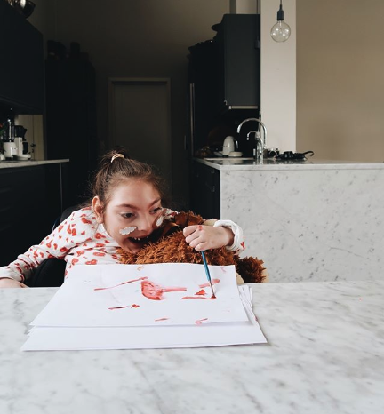 Ett av Ditte Svanfeldts barn sitter vid ett bord och målar med en röd färg
