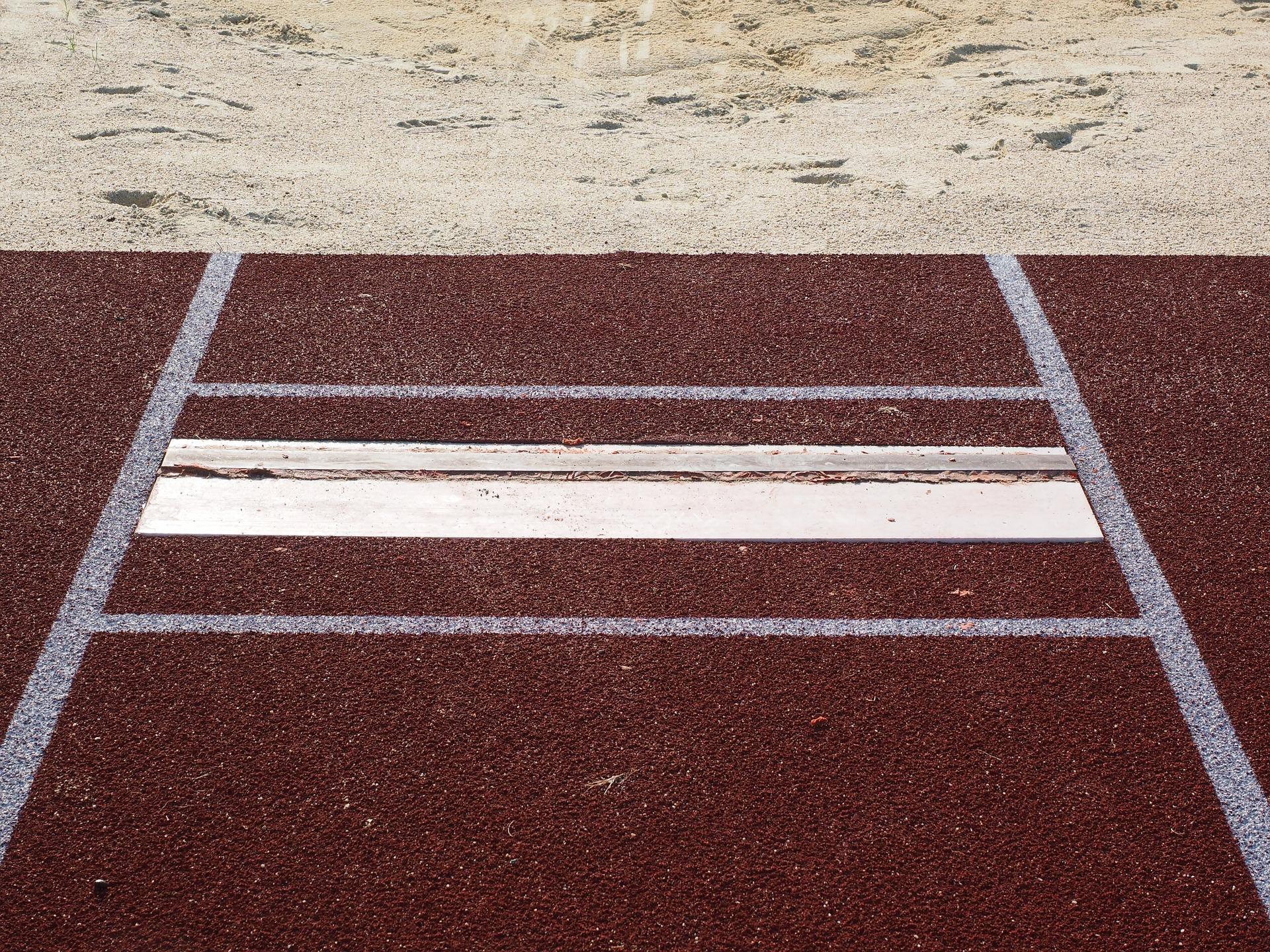 En längdhoppsplanka och längdhoppsgropen.