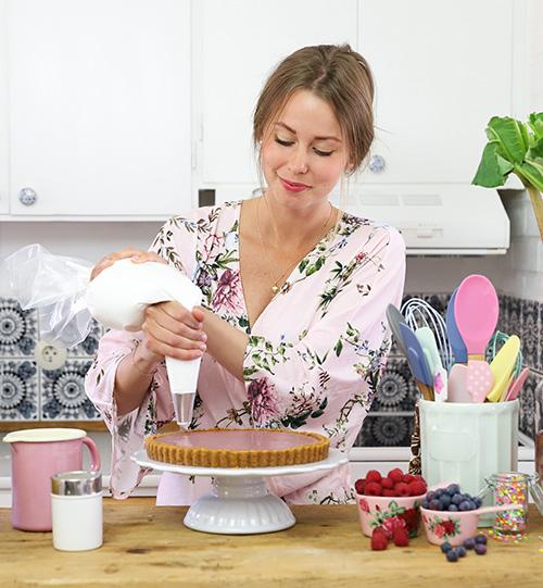 Frida Skattberg, som driver Baka med Frida, står i ett kök och spritsar på en paj