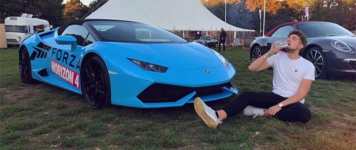 """Maurice """"L22"""" sitter i gräset vid en blå bil och dricker vatten"""
