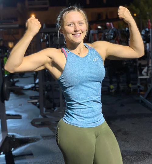 Ellen B Åkesson, som driver kontot Ajvie, i ett blått träningslinne ler och spänner musklerna