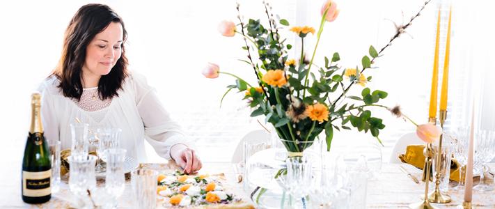 Jenny, som driver kontot Jennys Rum och Spis, står vid ett uppdukat bord