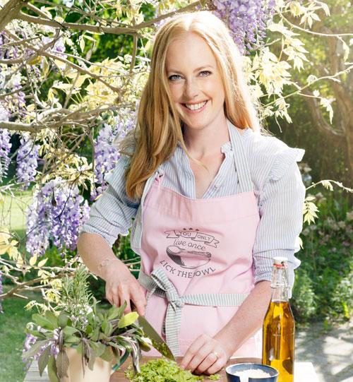 Helena Elm, som driver Bara en kaka till, står i en trädgård
