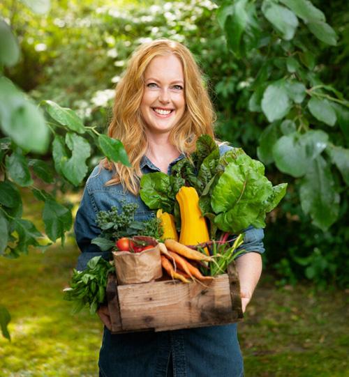 Helena Elm, som driver Bara en kaka till, står i en trädgård och håller en låda med grönsaker